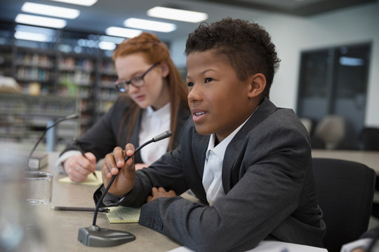 Boy middle school student talking into microphone in debate club