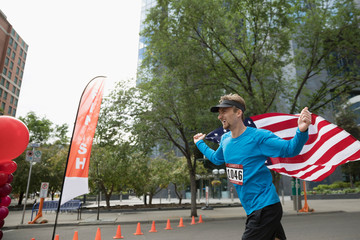 Male marathon runner running with American flag crossing finish line