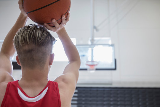 Male college basketball player shooting free throw in gymnasium