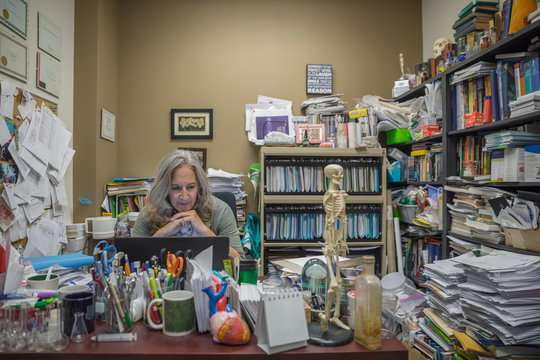 Female college science professor working at laptop in messy office