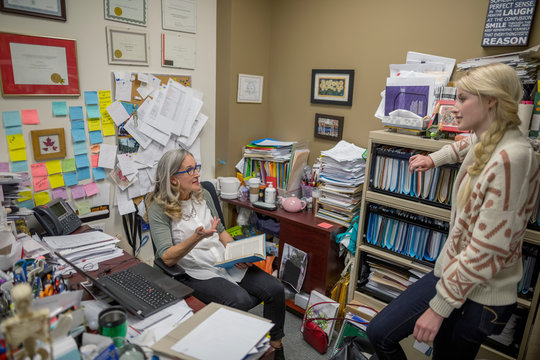 Female college professor and student talking in messy office