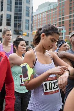 Female marathon runner checking smart watch, waiting at starting line on urban street