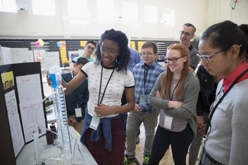 Middle school students watching scientific experiment at science fair