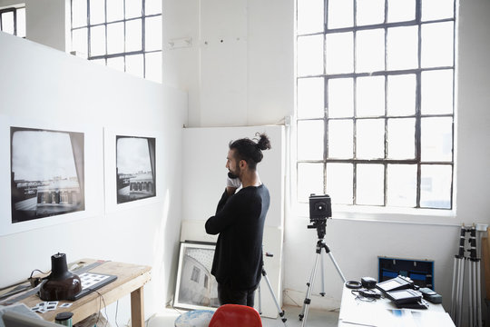 Focused male photographer examining large photography print hanging on wall in art studio