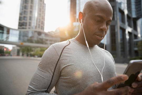 Male runner using smart phone, listening to music with earbud headphones on urban street