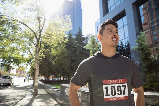 Male marathon runner wearing marathon bib on sunny urban sidewalk