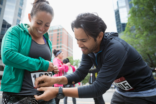 Husband helping smiling wife put on marathon bib on urban street