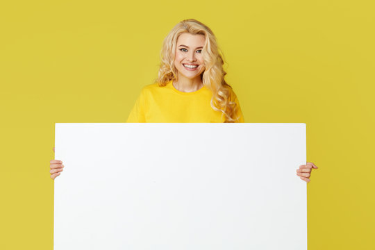Young happy woman peeks out from behind a white banner on a yellow background. Point to an empty blank on a form, a copy space for text. Horizontal shot