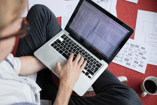 Businessman working on laptop on office floor