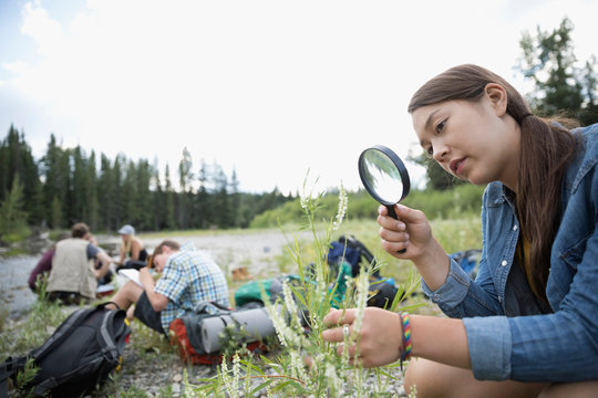 Curious teenage girl outdoor school student with magnifying glass examining wildflowers in nature
