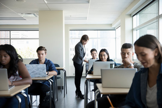 Professor helping college student at laptop in classroom