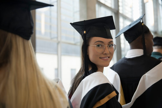 Portrait smiling, confident female college graduate student in cap and gown
