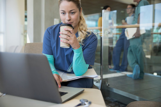 Female nurse drinking coffee, working at laptop in hospital lounge