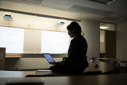 Female college professor with laptop in dark auditorium classroom