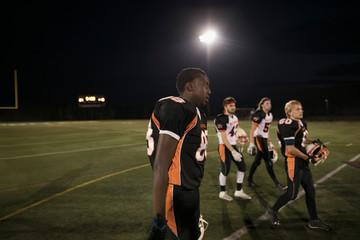 Teenage boy high school football players walking on football field