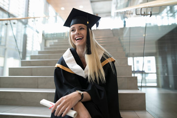 Laughing female college student graduate in cap and gown holding diploma on stairs