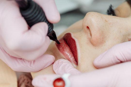 Woman having permanent makeup on lips in beauty salon