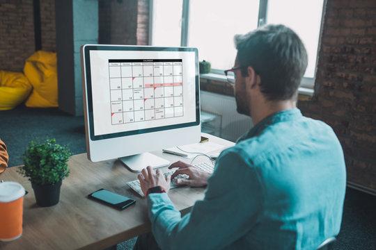 Nice smart man looking at the calendar