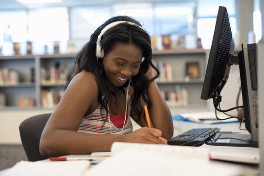Smiling college student with headphones studying, researching at computer in library
