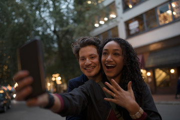 Young couple with camera phone taking selfie with engagement ring on urban night sidewalk