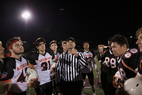 Teenage boy high school football teams watching referee perform coin toss on football field