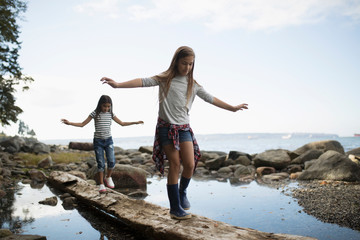 Girl friends walking, balancing on fallen log over water
