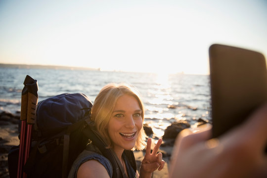 Smiling woman with hiking backpack gesturing peace sign, taking selfie with camera phone on sunny ocean beach
