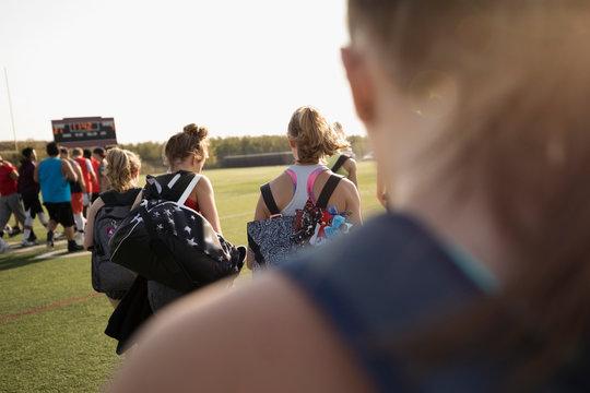 Teenage girl high school cheerleading team walking with bags on football field