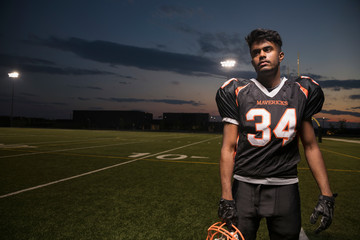 Portrait serious, tough teenage boy high school football player on football field at night