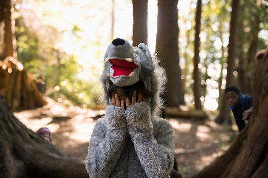 Portrait shy boy in wolf costume hiding head in hands in woods