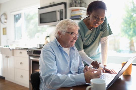 Female home nurse helping senior male patient reordering prescription medication at laptop