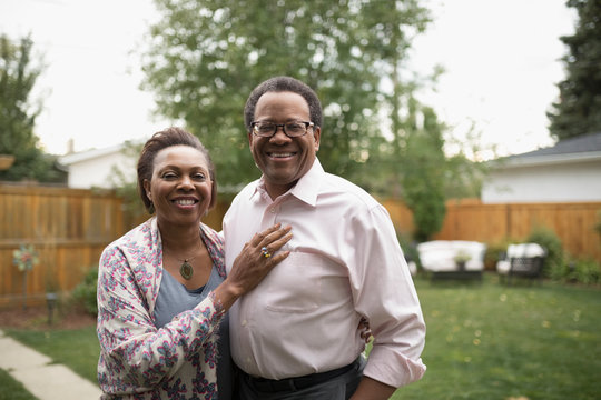 Portrait smiling senior couple hugging in backyard