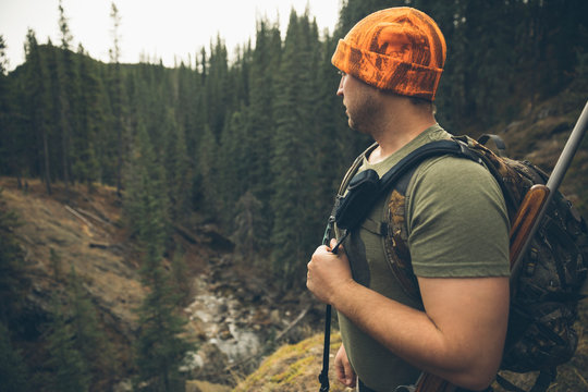 Male hunter in orange beanie with hunting rifle on forest ridge