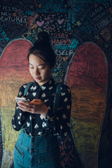 Asian tween girl texting with smart phone against wall with chalk angel wings