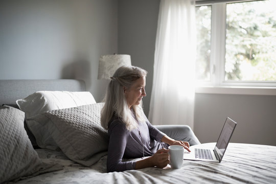 Senior woman drinking coffee and using laptop on bed
