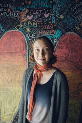 Portrait confident Caucasian tween girl against wall with chalk wings