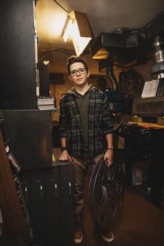 Portrait confident Caucasian tween boy projectionist holding film reel in movie theater