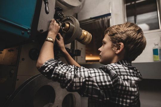 Caucasian tween boy projectionist loading film reel in movie theater