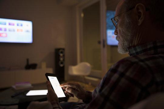 Senior man using smart TV apps on smart phone in dark living room