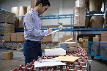 Male warehouse manager with clipboard checking packages on production line conveyor belt