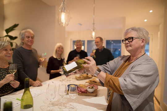 Senior woman hosting wine tasting party, showing wine bottle at dining table