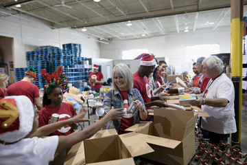Volunteers in Santa hats filling Christmas donation boxes in warehouse