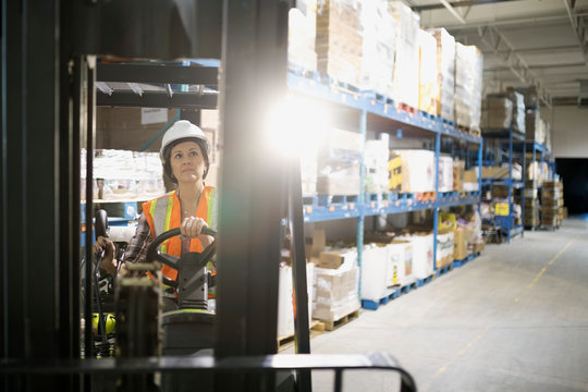 Female worker driving forklift in distribution warehouse