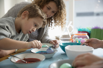 Mother watching focused son dyeing Easter egg, dipping in blue Food coloring