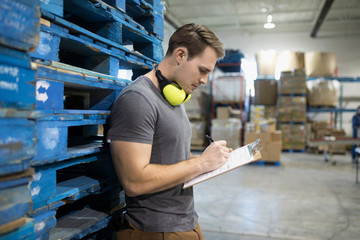 Male worker with clipboard in distribution warehouse
