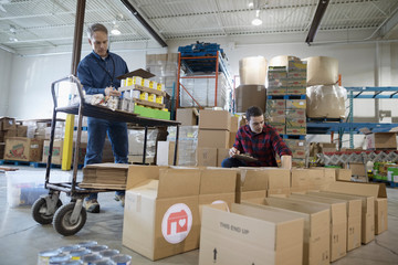 Male volunteers with canned Food filling donation boxes in warehouse