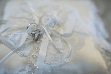 Close up still life wedding rings tied to white satin wedding pillow