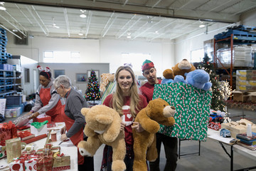 Portrait smiling female volunteer carrying teddy bear toys in warehouse