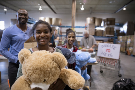 Portrait smiling father and daughters donating toys in warehouse