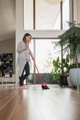 Woman sweeping hardwood floors with broom